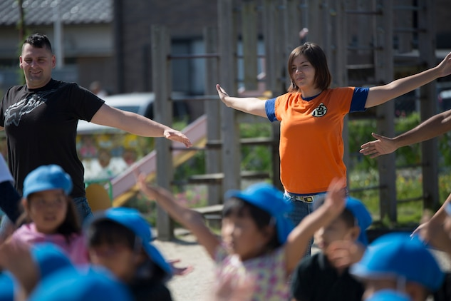 Cpl. Tiffany Ackerman, an air freight clerk with Headquarters and Headquarters Squadron, follows along with preschoolers to a dance routine at Kawashimo Preschool, Iwakuni, Yamaguchi Prefecture, Japan, Sept. 29, 2015. Service members from Marine Corps Air Station Iwakuni volunteered to come out to the preschool to show they are a part of the community and bond with them as well.