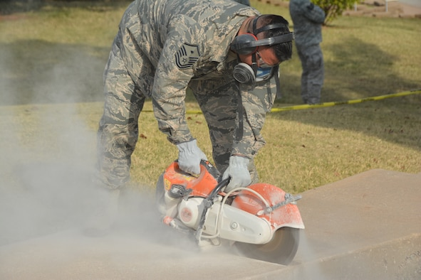 Master Sgt. Juan Escobar, 507th Civil Engineer 1st Sgt., cuts away at the sidewalk Oct. 3, 2015, at Tinker Air Force Base, Okla. The team used a combination of heavy equipment, circular saws and hand tools to tear out an unsafe concrete stairway, and covered the newly exposed earth with sod. (U.S. Air Force photo/Senior Airman Krystin Trosper)