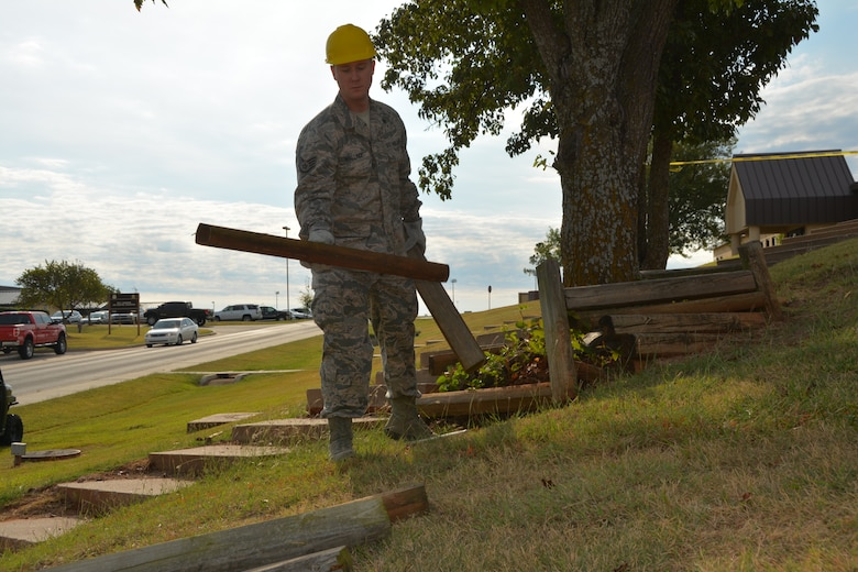 Staff Sgt. Michael Wallace of the 507th Civil Engineer Squadron removes landscaping timbers located next to a soon-to-be demolished stairway Oct. 3, 2015, at Tinker Air Force Base, Okla. The stairway was removed as a safety precaution, since the stairway cracked over time and became uneven and unsafe. (U.S. Air Force photo/Senior Airman Krystin Trosper)