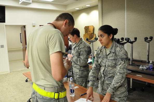 Senior Airman Eloisa Paez of the 507th Medical Squadron's Drug Demand Reduction team waits as an Airman verifies his information on his urine sample during urinalysis testing Oct. 3, 2015, at Tinker Air Force Base, Okla. The 507th MDS is required to test 100 percent of the Reservist population each year. (U.S. Air Force photo/Tech. Sgt. Charles Taylor)