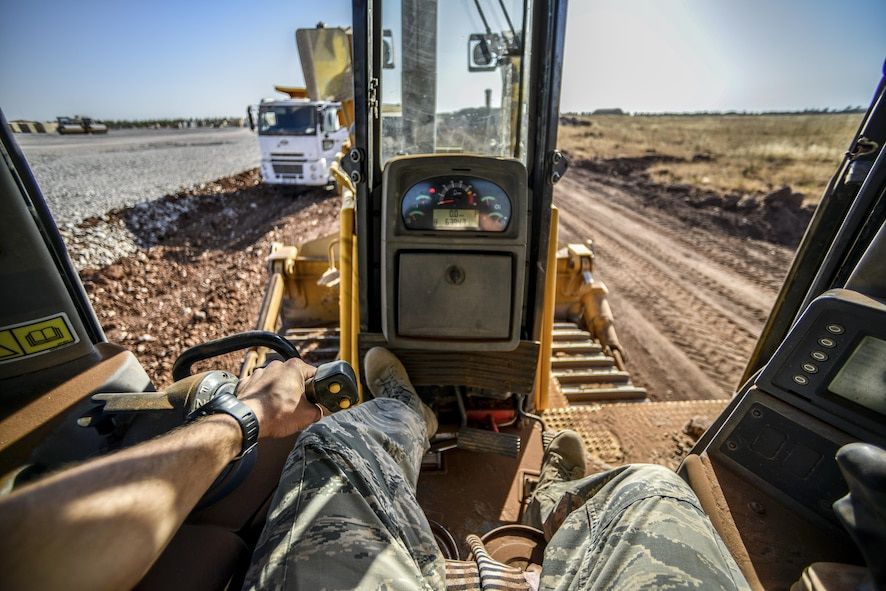 Staff Sgt. Logan Pals, a 435th Construction Training Squadron pavements and construction equipment operator, sits in the seat of a bulldozer while waiting for gravel to be dumped Sept. 24, 2015, at Diyarbakir Air Base, Turkey. The 435th CTS have more than 10 construction vehicles that are used to dump, move, grade and roll gravel throughout the base. (U.S. Air Force photo/Airman 1st Class Cory W. Bush)