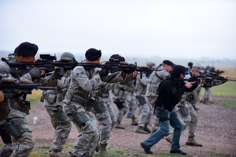 Members of the 28th Security Forces Squadron move at the low-ready position during a shoot, move, communicate training event at Ellsworth Air Force Base, S.D., Sept. 29, 2015. Airmen and civilian security forces members practiced engaging their targets, communicating and protecting one another on a simulated battlefield. (U.S. Air Force photo/Airman 1st Class James L. Miller)