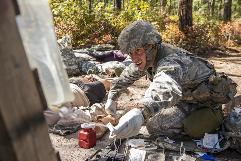 Capt. Richard Pate, a Walter Reed National Military Medical Center nurse, checks an IV for a simulated patient during an Expert Field Medical Badge competition at Joint Base McGuire-Dix-Lakehurst, N.J., Oct. 6, 2015. The competition candidates had to run through a tactical combat care course while evading simulated attacks and attending to patients. (U.S. Air Force photo/Senior Airman Tara A. Williamson)