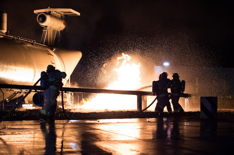Firefighters and base leadership demonstrate extinguishing an aircraft fire Oct. 8, 2015, at Ramstein Air Base, Germany. As part of Fire Prevention Week, families visited Fire Station 1 to learn about fire safety, including home-fire safety issues, fire extinguisher training and holiday safety tips. (U.S. Air Force photo/Senior Airman Damon Kasberg)