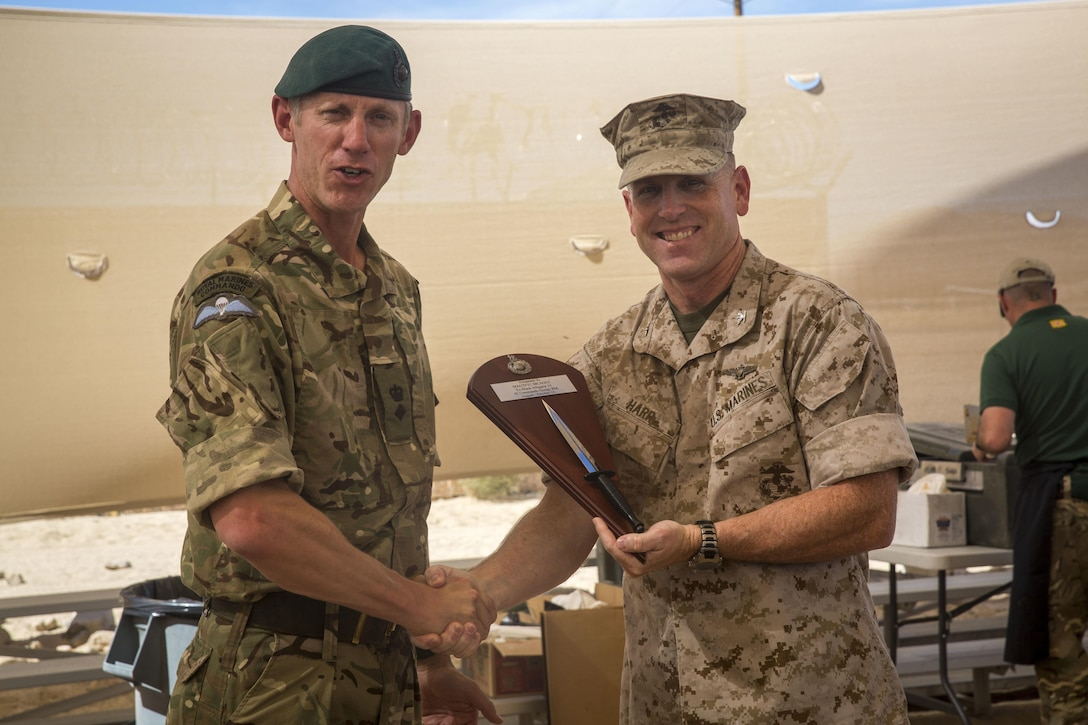 British Royal Marine Lt. Col. Richard Cantrill, commanding officer, 42 Commando, 3 Commando Brigade, presents Combat Center Chief of Staff, Col. James F. Harp, with a plaque to show his thanks for the opportunity to train aboard the installation during a barbeque lunch concluding Black Alligator 15 at Camp Wilson, Oct. 8, 2015. (Official Marine Corps photo by Lance Cpl. Levi Schultz/Released)