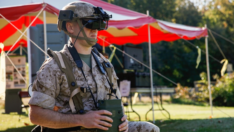 Captain Jerry Feehary, the fires project officer for Marine Corps Warfighting Laboratory, calls for simulated fire during the Augmented Immersive Team Training demonstration for Marine leadership and key civilian leaders at the Medal of Honor Golf Course, Marine Corps Base Quantico, Virginia, Oct. 14, 2015. The system provides a virtual battlefield complete with aircraft and artillery to engage ground vehicles and personnel with no needs for concerns such as safety, resources or availability of ranges for realistic training.