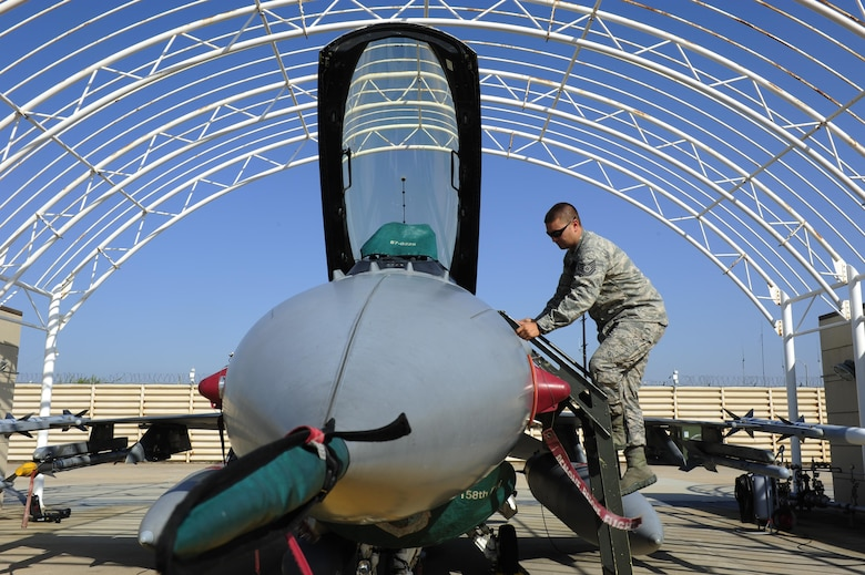 U.S. Air Force Tech. Sgt. Brett Larson, 134th Expeditionary Fighter Squadron F-16 Fighting Falcon crew chief, Vermont Air National Guard, climbs a ladder to inspect the cockpit of an F-16 at Kunsan Air Base, Republic of Korea, Oct. 6, 2015. The 134th EFS was redeployed from Kadena Air Base, Japan to Kunsan AB as part of a theater security package. Movement of TSPs into the Pacific region is a routine and integral part of U.S. Pacific Command's force posture. (U.S. Air Force photo by Staff Sgt. Nick Wilson/Released)