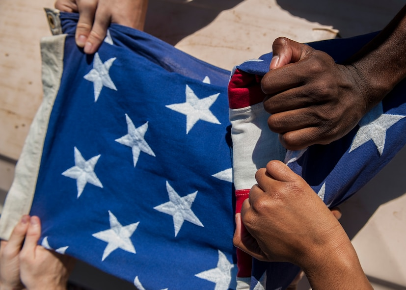 Members of the Nellis Air Force Base Honor Guard practice the ceremonious folding of the U.S. flag at Nellis AFB, Nev., Oct. 13, 2015. The team utilizes either the two-person or six-person flag folding sequence during a retirement or funeral. (U.S. Air Force photo by Staff Sgt. Siuta B. Ika)