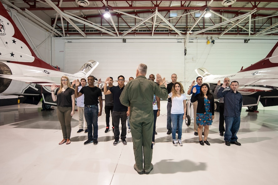 """Col. Ross R. Anderson (foreground, center), 926th Wing commander, administers the oath of enlistment to future Airmen of the 926th WG at Thunderbird Hangar on Nellis Air Force Base, Nev., Oct. 9, 2015. The 926th WG is headquartered at Nellis AFB and consists of two groups, 12 squadrons and one detachment located across the nation. Through Total Force Integration, reservists are integrated into regular Air Force units, accomplishing the U.S. Air Force Warfare Center and 432nd Wing/432nd Air Expeditionary Wing missions side-by-side regular Air Force personnel on a daily basis. During the swearing-in ceremony, Anderson said """"I'm envious of the adventures, challenges, successes and life-events that they are going to experience in their time in the Air Force. They have joined an elite culture, and they get to look forward to working with the best people in the greatest military to have ever existed."""" (U.S. Air Force photo by Staff Sgt. Siuta B. Ika)"""