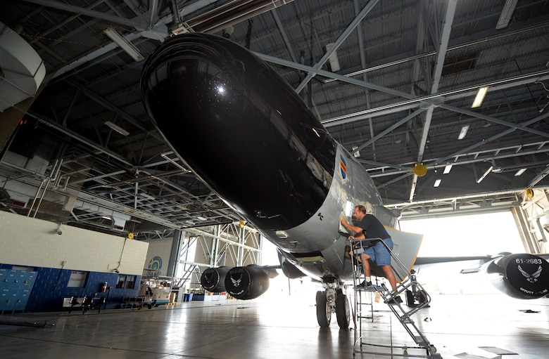 James Battig, a fabrication work leader with the 55th Maintenance Squadron, delicately places the first of many nose art pieces onto an RC-135S Cobra Ball while parked in dock 4 of the Bennie Davis Maintenance Facility on Sept. 2, Offutt Air Force Base, Neb.  The Cobra Ball had the first higher headquarters approved art, a serpent tightly coiled around a black sphere.  (U.S. Air Force Photo by Josh Plueger/Released)