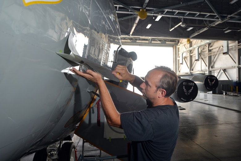 James Battig, a fabrication work leader with the 55th Maintenance Squadron, carefully reveals the inaugural piece of nose art that on an RC-135S Cobra Ball aircraft on Sept. 2, Offutt Air Force Base, Neb.  Members of the 55th Maintenance squadron are responsible for commissioning the art pieces that will grace the noses of the RC fleet.  (U.S. Air Force Photo by Josh Plueger/Released)