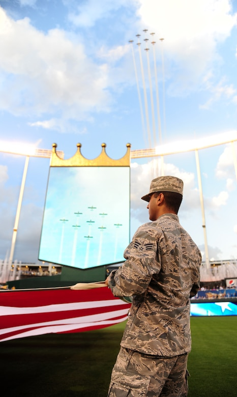 Senior Airman Aditya Venkatapur, 509th Force Support Squadron fitness center front desk clerk, holds the flag before the start of the American League Divisional Series at Kauffman Stadium in Kansas City, Mo., Oct. 8, 2015. More than 20 service members held the flag during the singing of the National Anthem. (U.S. Air Force photo by Senior Airman Joel Pfiester/Released)