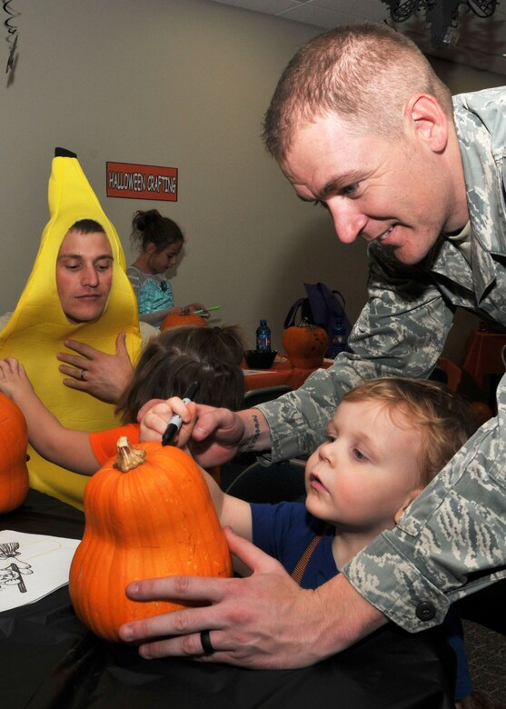 An Airman helps his son draw on a pumpkin during the Montana Air National Guard Airman and Family Readiness Program Halloween party held for children of guardsmen at the 120th Airlift Wing in Great Falls, Mont., Oct. 14, 2015.  (U.S. Air National Guard photo by Senior Master Sgt. Eric Peterson/Released)