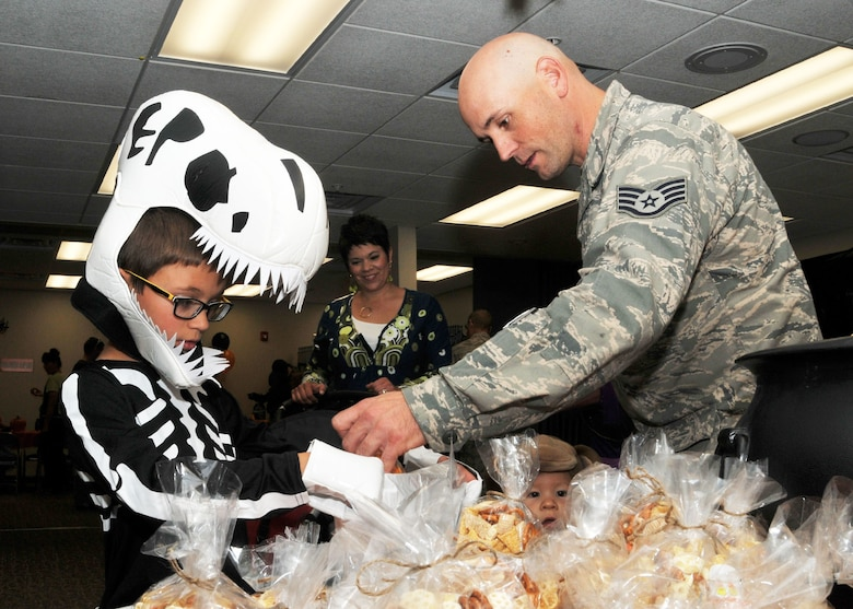 A child dressed as a dinosaur receives a treat from his father during the Montana Air National Guard Airman and Family Readiness Program Halloween party held for children of guardsmen at the 120th Airlift Wing in Great Falls, Mont., Oct. 14, 2015. (U.S. Air National Guard photo by Senior Master Sgt. Eric Peterson/Released)