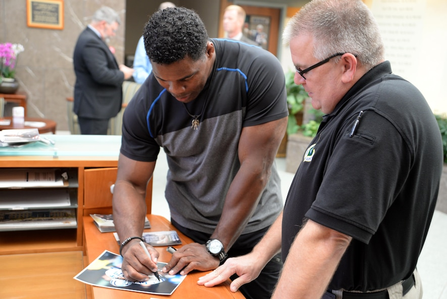 Former NFL player, Herschel Walker signs an autograph for Ed Conway, Air Force Mortuary Affairs Operations mortuary specialist, during a visit Oct. 15, 2015 to the Charles C. Carson Center for Mortuary Affairs, Dover Air Force Base, Del. Walker expressed his gratitude to the men and women of AFMAO for the work they do for the nation's fallen service members. (U.S. Air Force photo/Tech. Sgt. Jose Contreras)