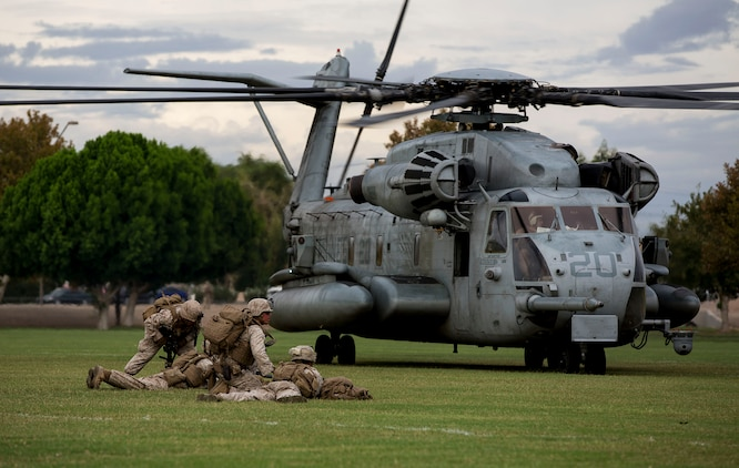 Marines with 2nd Battalion, 7th Marine Regiment, based out of Marine Corps Air Ground Combat Center Twentynine Palms, Calif., provide security in front of a CH-53E Super Stallion helicopter during a non-combatant evacuation exercise at Kiwanis Park in Yuma, Ariz., Friday, Oct. 16, 2015. The Marines reinforced initial ground units preparing for the evacuation.
