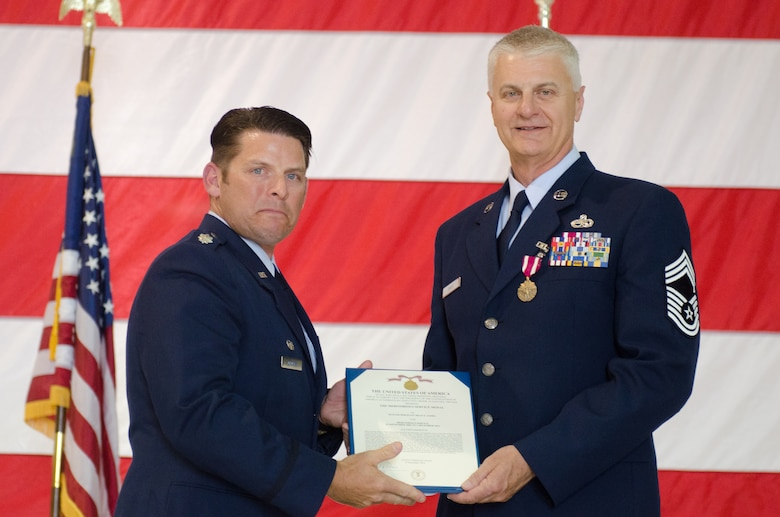 Chief Master Sgt. William K. Davis (right), the outgoing component maintenance flight chief of the 123rd Maintenance Squadron, receives the Meritorious Service Medal from Lt. Col. Ash Groves, commander of the 123rd Maintenance Squadron, during Davis' retirement ceremony at the Kentucky Air National Guard base in Louisville, Ky., May 16, 2015.  Davis ends his career with more than three decades in the Kentucky Air National Guard. (U.S. Air National Guard photo by Senior Airman Joshua Horton)