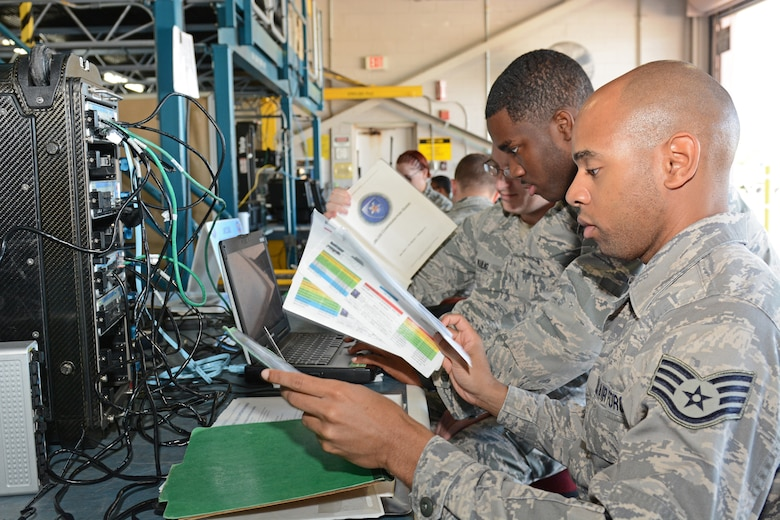 "U.S. Air Force Staff Sgt. Darius Carter and Airman Ahkeen Benjamin with help from others in the 290th Joint Communication Support Squadron ""B-Flight"" troubleshoot the setup and configuration of a JBlox baseband equipment at MacDill Air Force Base, Tampa Fla., May 3, 2015. The JBlox baseband equipment is used to connect phones and computers to satellite systems. (U.S. Air Force photo by Staff Sgt. Troy Anderson/ RELEASED)"