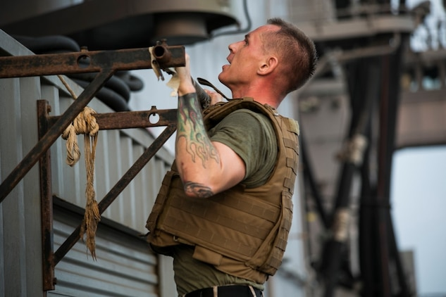 ARABIAN GULF (Oct. 17, 2015) U.S. Marine Staff Sgt. Joshua Milhorn does pull-ups during a corporals course physical training event aboard the amphibious assault ship USS Essex (LHD 2). Milhorn is an aviation ordnance system technician with Marine Aviation Logistics Squadron 13, Marine Medium Tiltrotor Squadron 161 (Reinforced), 15th Marine Expeditionary Unit. Milhorn has instructed every corporals course hosted on ship because he likes having an influence on the future leaders of the Marine Corps. The 15th MEU, embarked aboard the ships of the Essex Amphibious Ready Group, is deployed to maintain regional security in the U.S. 5th Fleet area of operations. (U.S. Marine Corps photo by Cpl. Anna Albrecht/ Released)