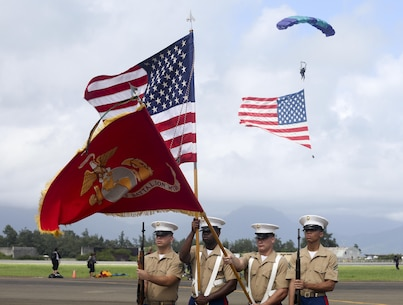 The Marine Corps Base Hawaii Color Guard present colors during the national anthem as a parachutist with the U.S. flag descends to begin the 2015 Kaneohe Bay Air Show and Open House aboard Marine Corps Base Hawaii, Oct. 18, 2015. The mission of MCB Hawaii is to provide facilities, programs and services in direct support of units, individuals and families in order to enhance and sustain combat readiness for all operating forces and tenant organizations. (U.S. Marine Corps photo by Cpl. Ricky S. Gomez)