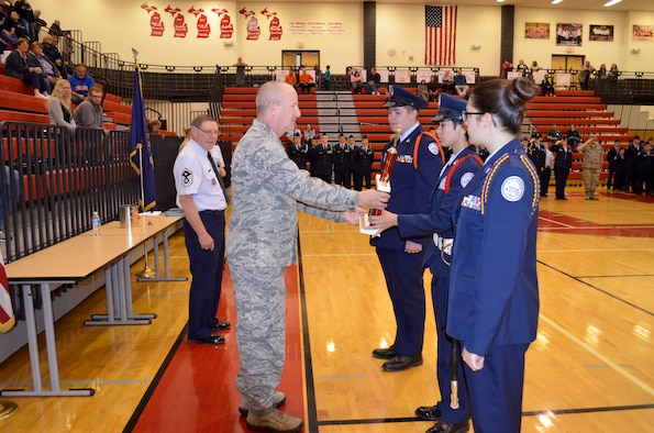 Brig. Gen. John D. Slocum, commander of the 127th Wing, presents an award to three Anchor Bay Junior ROTC cadets that came together for drill team competitions on Otc. 17, 2015, at Anchor Bay High School in Michigan. Ten teams of approximately 25 cadets meet to compare professional abilities against one another exhibiting the capability to work as a team, perform in a stressful environment, and display discipline.