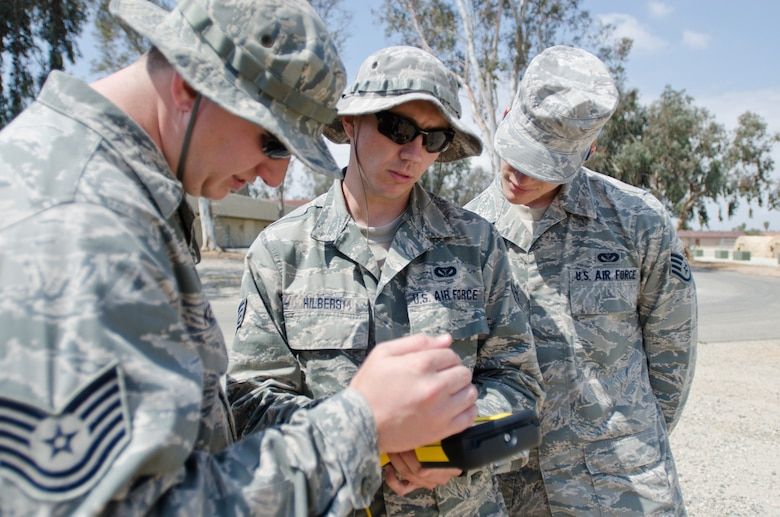 Tech Sgt. Nick Ketterer (left), Staff Sgt. Abe Hilbers (center) and Staff Sgt. Daniel Brooks (right), all Airmen from the Kentucky Air National Guard's 123rd Civil Engineer Squadron, use surveying equipment during a training scenario at March Air Reserve Base, Calif., on June 10, 2015. The exercise was designed to simulate a real-world mission. (U.S. Air National Guard photo by Senior Airman Joshua Horton)