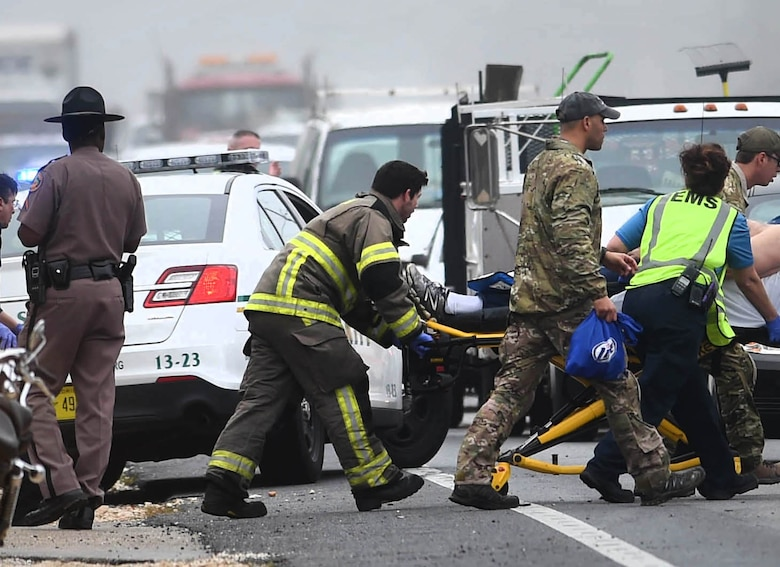 A pararescue Airman from the Kentucky Air National Guard's 123rd Special Tactics Squadron assists an injured motorist following a traffic accident in Florosa, Fla., March 3, 2015. The Airman was later recognized with a Community Service Award from the Okaloosa Country Sheriff's Department for his actions. (Photo by Nick Tomecek, Northwest Florida Daily News)