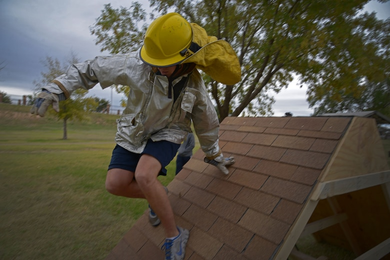 A U.S. Air Force Airman with the 27th Special Operations Support Squadron leaps over a wall as part of an obstacle course during the 16th Annual Squadron Fire Muster Oct. 16, 2015, at Cannon Air Force Base, N.M. Six teams from various squadrons across the 27th Special Operations Wing came together to compete in this year's muster. (U.S. Air Force photo/Staff Sgt. Alexx Pons)