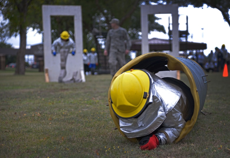 A U.S. Air Force Airman with the 27th Special Operations Civil Engineer Squadron low crawls through a tube as part of an obstacle course during the 16th Annual Squadron Fire Muster Oct. 16, 2015, at Cannon Air Force Base, N.M. Six teams from various squadrons across the 27th Special Operations Wing came together to compete in this year's muster. (U.S. Air Force photo/Staff Sgt. Alexx Pons)