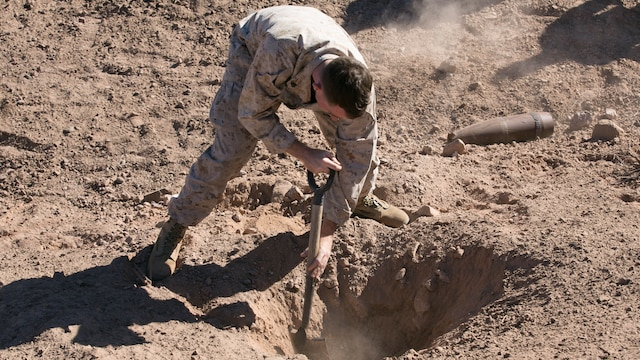 Sgt. Brendan Campbell, on-the-job trainee, Explosive Ordnance Disposal, digs out loose dirt from a hole created from an M2A4 shaped charge at Rainbow Canyon Training Area, Oct. 8, 2015. The first day of the excavation was used as training for EOD while also helping the Natural Resources and Environmental Affairs Division create a water source for wildlife aboard the Combat Center.