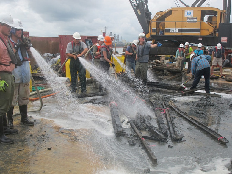 """Archaeologists with Panamerican Consultants, Inc. spray down pieces of the CSS Georgia's armor or """"casemate"""" during the mechanized recovery phase, Sept. 24. The mechanized recovery is one of the final phases of the project that will remove the ironclad before deepening the Savannah harbor."""