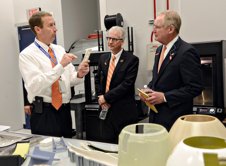 Martin Williams, the 76th Commodities Maintenance Group engineering branch chief, shows parts made using 3-D printing technology in the reverse engineering and critical tooling cell to Dr. Charles Bunting, associate dean of Research and Sponsored Programs at Oklahoma State University, and Dr. Burns Hargis, OSU president, during a tour of OC-ALC engineering and software facilities Oct. 7, 2015. (Air Force photo/Kelly White)