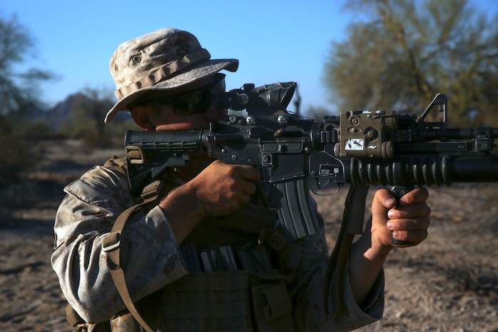 Lance Cpl. Henry Mesker, a rifleman assigned to Company E, 2nd Battalion, 7th Marine Regiment, 1st Marine Division, searches for enemy targets after a simulated attack in the defense  during Talon Exercise 1-16 at Marine Corps Air Station, Yuma, Ariz., Oct. 13, 2015. The training took place at Baker's Peak, a rugged desert training area located on the approximately 1,700,000 acre Barry M. Goldwater Range and was part of a larger event called Talon Exercise, which focused on offensive and defensive operations in desert and urban environments.