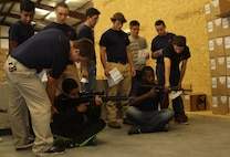 Poolees from Marine Corps Recruiting Sub-station Aberdeen, North Carolina, correct each other's seated position during a pool function at Quantico Tactical in Aberdeen, North Carolina, Oct. 10, 2015. The Marines taught the poolees proper weapons handling, aiming and marksmanship to give them a unique experience and teach them skill sets that will be useful at recruit training. (U.S. Marine Corps photo by Sgt. Dwight A. Henderson/Released)