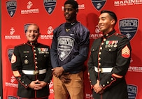 Bullis School senior, Cameron Brown, stands with U.S. Marine Corps Staff Sgt. Raymond Guzman-Ortiz, left, and Sgt. William Ramos-Sorto, right, recruiters with Recruiting Sub-station Rockville during Brown's Semper Fidelis All-American Bowl selection jersey presentation Oct. 13, 2015, at Bullis School auditorium in Potomac, Maryland. The Semper Fidelis Football Program focuses on mentoring exceptional youth athletes and future leaders by collectively celebrating academic excellence, proven physical fitness and quality of character. Brown, from Burtonsville, Maryland, will play in the televised game Jan. 3, 2016 in Carson, California. (U.S. Marine Corps photo by Sgt. Anthony J. Kirby/Released)