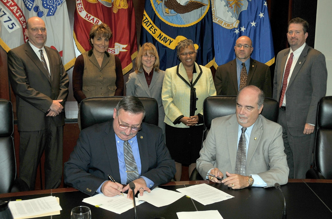 (From left) Defense Logistics Agency Vice Director Ted Case and DLA Finance Director Anthony Poleo sign three audit readiness assertion letters while DLA senior leaders (center) look on during a Sept. 29 Senior Executive Service Summit at the McNamara Headquarters Complex.