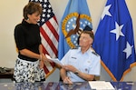 Defense Logistics Agency Director Air Force Lt. Gen. Andy Busch hands the agency's signed assertion letters to Simone Reba, deputy director of DLA Finance Sept. 30. The letters, which state that the agency's financial statements are ready for its first full audit, will now be sent to the Office of the Under Secretary of Defense (Comptroller) for review and approval.