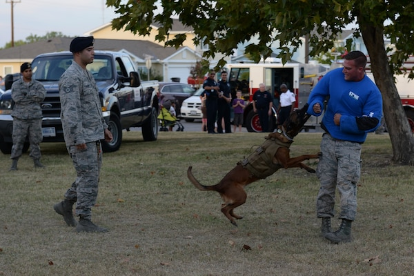 Military Working Dog Sonja attacks Senior Airman Travis Counts, 802nd Security Forces Squadron MWD handler, as her handler, Staff Sgt. Paul Olmos, 802nd SFS, watches on as part of a demonstration during National Night Out Oct. 6, 2015, at Joint Base San Antonio-Lackland, Texas. At the annual event there was also a bouncy castle, police cars, fire trucks, a Humvee, face painting station, firearms display, a station that taught how to use a taser and a station that taught children scare away attackers with a baton. (U.S. Air Force photo by Senior Airman Krystal Wright/Released)