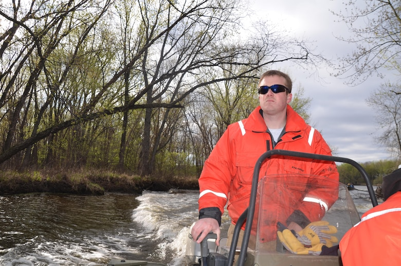 Brandon Olson, operations, watches the cold water rescue training as he operates a small boat.