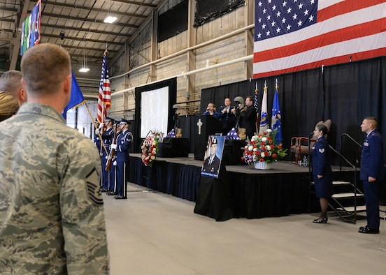 The Voices of Hanscom (from left) Michael Fields, Stacey Jones, Maj. Catherine Tobin and Andie Avram perform the National Anthem on stage during a memorial service at the Aero Club Hangar at Hanscom Air Force Base, Mass., Oct. 16. The service was held to honor Senior Airman Nathan Sartain and Senior Airman Kcey Ruiz, who were killed Oct. 2, when the C-130J Super Hercules they were on crashed shortly after takeoff from Jalalabad, Afghanistan. (U.S. Air Force photo/Jerry Saslav)