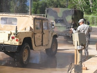 Soldiers using the Schofield Barracks Centralized Wash Facility to remove dirt and potential plant propagules from Humvee. Using a high pressure low volume wand ensures minimal water utilization and maximum debris removal. Effluent for this facility is recycled through a grit chamber, oil chamber, and through a series of sand and membrane.