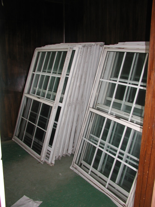 Windows that have been removed from a building are stacked and saved for sale or reuse.
