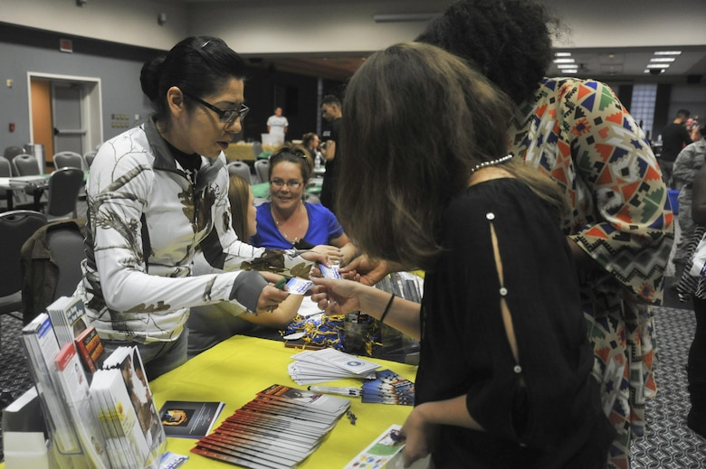 U.S. Air Force Senior Airman Victoria Gutierrez, 17th Medical Operations Squadron Mental Health technician, passes out information on mental health at the Event Center on Goodfellow Air Force Base Oct. 8, 2015. The information was passed out for the 5th annual Girl's Night Out. (U.S. Air Force photo by Airman Chase Sousa/Released)
