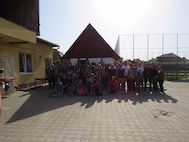 Members of the 123rd Expeditionary Fighter Squadron gather for a photography with children at a local orphanage near Campia Turzii, Romania, Sept. 19, 2015. (Photo courtesy of 123rd Expeditionary Fighter Squadron)