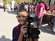 A Romanian child holds a camera while members of the 123rd Expeditionary Fighter Squadron spend the day at a local orphanage near Campia Turzii, Romania, Sept. 19, 2015. (Photo courtesy of 123rd Expeditionary Fighter Squadron)