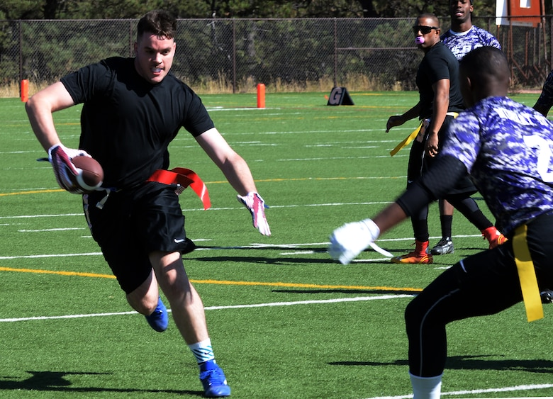 Kevin Tufts, 90th Missile Security Forces Squadron, attempts to avoid a defenseman from Fort Carson, Colo., during a flag football game Oct. 17, 2015, at the U.S. Air Force Academy, Colo. The Warren team played four games throughout the day, making it to the championship game where the faced Fort Carson for a second time. (U.S. Air Force photo by Senior Airman Brandon Valle)
