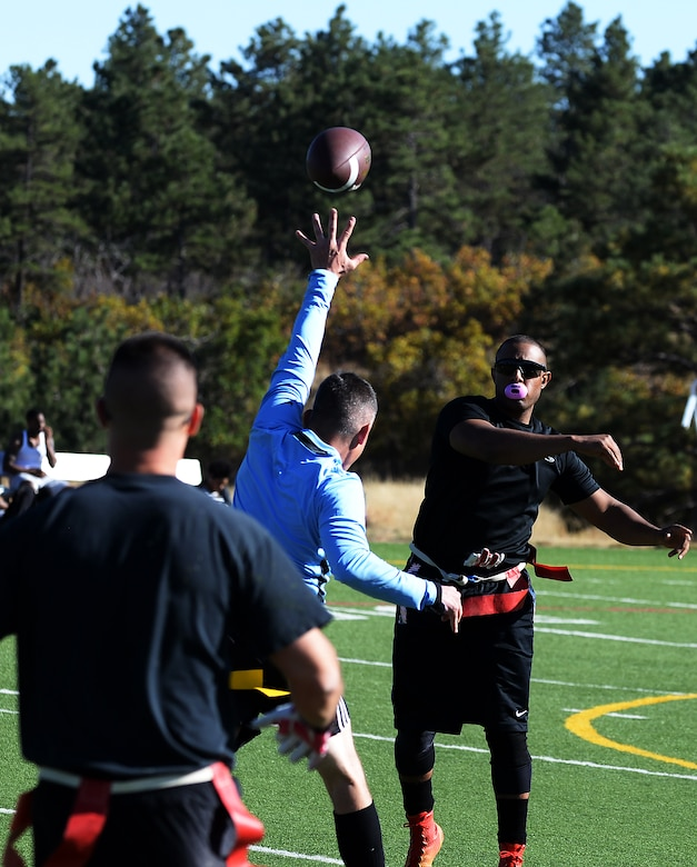 Nicolas Sisco, 90th Missile Maintenance Squadron Electrical Maintenance Team technician, runs past defensemen from Fort Carson, Colo., during a flag football game Oct. 17, 2015, at the U.S. Air Force Academy, Colo. The Warren team came in second in the tournament, falling to the undefeated team from Fort Carson, Colo. (U.S. Air Force photo by Senior Airman Brandon Valle)
