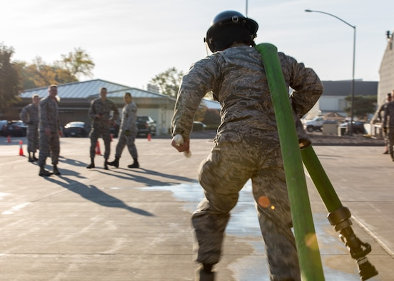 An airman assigned to the 366th Civil Engineer Squadron drags a firehose during the 3rd annual CE Readiness Challenge Oct. 15, 2015 at Mountain Home Air Force Base, Idaho. 10 teams of airmen from various sections of the squadron competed against each other for a shot at first place recognition. (U.S. Air Force photo by Airman 1st Class Connor J. Marth)
