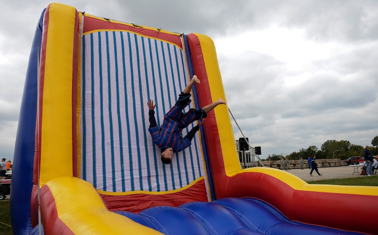 U.S. Air Force Airman 1st Class Austin Moriarty, 509th Munitions Squadron weapons maintenance team member, performs a flip on the velcro wall fling during Wingman Day, Oct. 9, 2015, at Whiteman Air Force Base, Mo. Events were held throughout the day to inform and educate Airmen about available resources and the importance of resiliency. (U.S. Air Force photo by Senior Airman Sandra Marrero/Released)