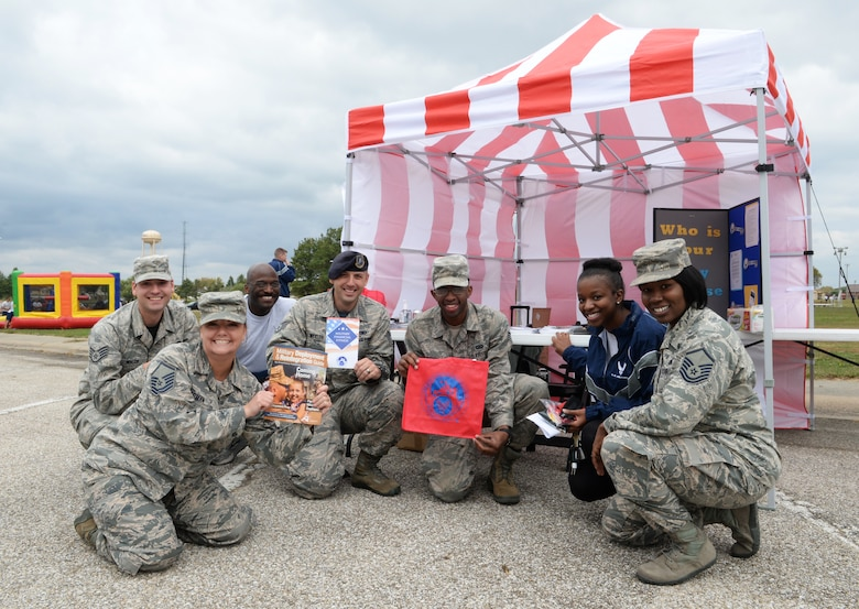 Whiteman Warriors pose in front of the Airman and Family Readiness Center (A&FRC) booth during Wingman Day, Oct. 9, 2015 at Whiteman Air Force Base, Mo. The A&FRC is just one resource available to Airmen that provides information, education, training and support programs to enhance resiliency. (U.S. Air Force photo by Tech. Sgt. Miguel Lara III/Released)